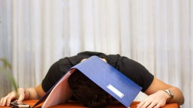 a man lying on a desk with a folder over his head