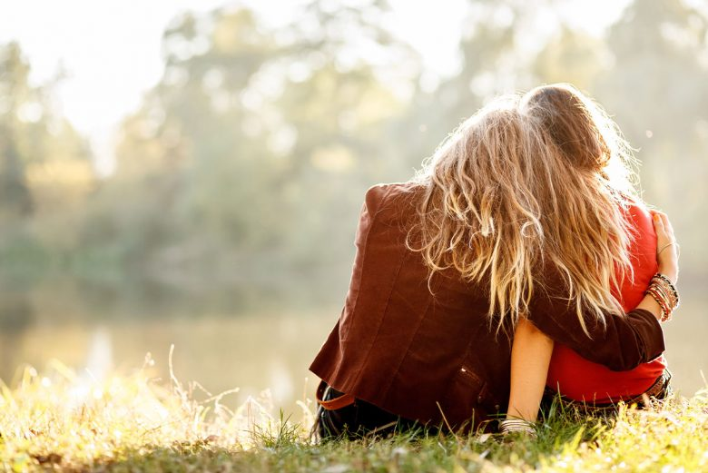 What it means to forgive - two women sitting on grass together