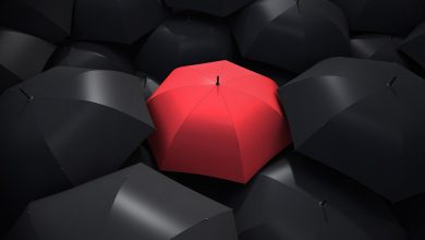 Red umbrella among black umbrellas - protect your energy from toxic people