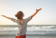 Woman looking out to the ocean with arms outstretched