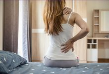 Woman sitting up in bed with neck and back pain