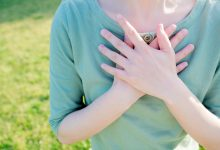 Does Energy Healing Really Work? Woman with hands over heart