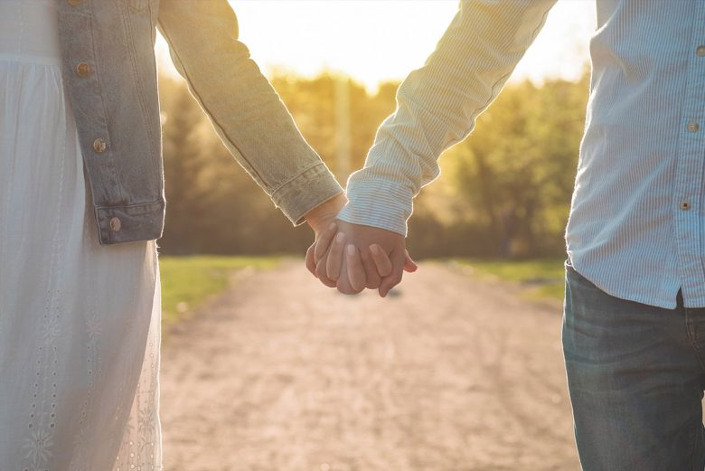 Woman and man holding hands as the walk down a path