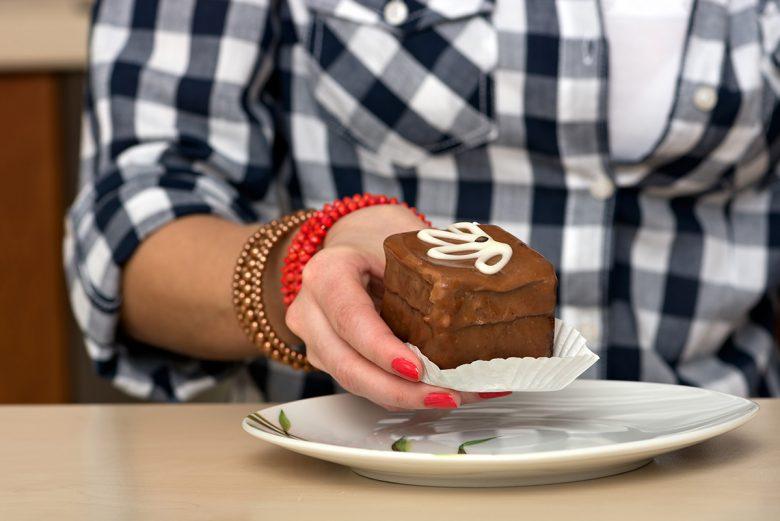 Woman holding piece of chocolate cake