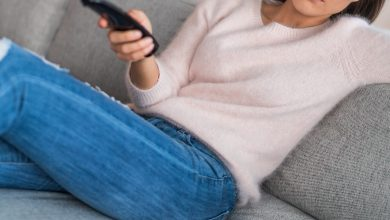Woman sitting on couch holding remote