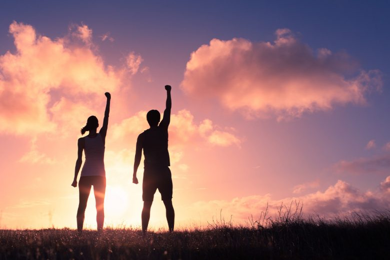 Woman and man standing strong - silhouette in front of sunset