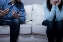 Man and woman sitting on a couch arguing
