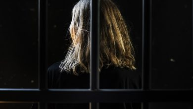 Blonde woman behind bars