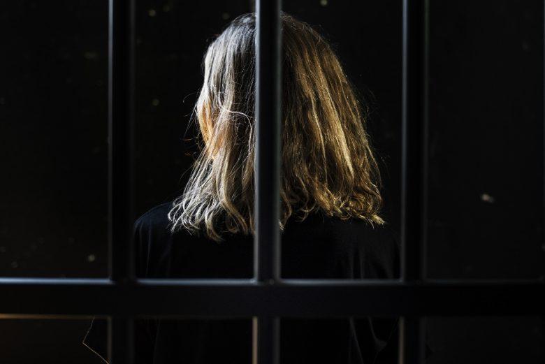 Blonde woman behind bars