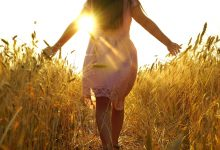 Woman walking through fields into the sunset- how to finally heal a lifelong pattern