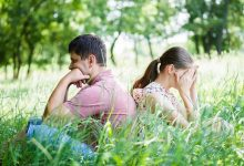Man and woman sitting back to back in field of grass