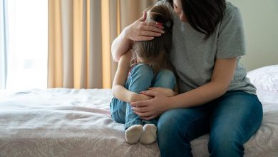 Mother comforting child on bed - how to protect your child from negative energy