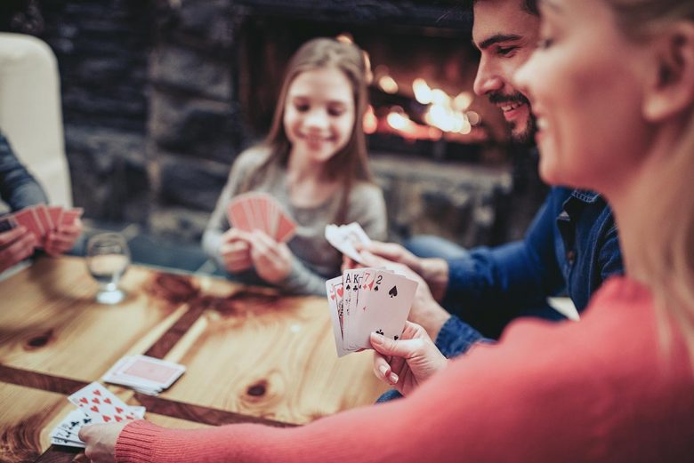 Family gathered around table playing cards - hidden blessings of 2020
