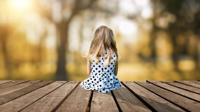 A little young girl is sitting on a wooden pier