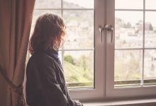Woman with wavy hair looking out a window on a quaint city