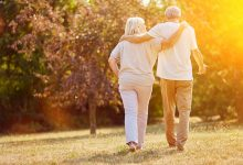 Man and woman walking with arms around each other during golden hour