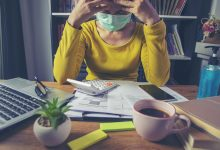 Woman at desk with mask on, stressed out