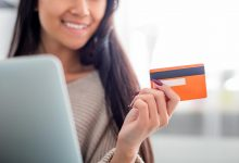 Woman smiling at laptop holding credit card