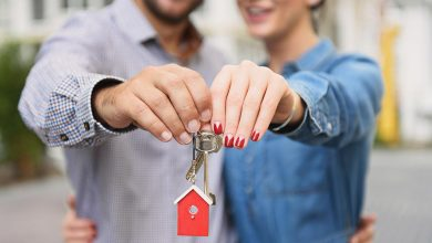 Couple holding a key to their new home - how to beat the housing market and find a home you love