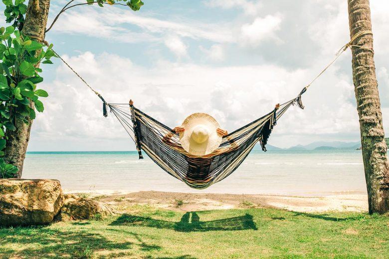 Woman relaxing in hammock by the ocean