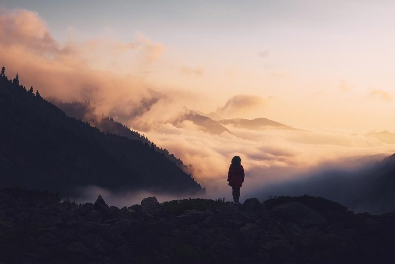 How to recover and fully heal after divorce - woman standing in nature among mountains